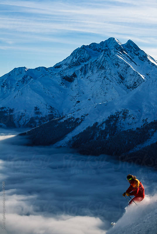 Man skiing in powder snow above the clouds in the winter mountains by Søren Egeberg Photography for Stocksy United