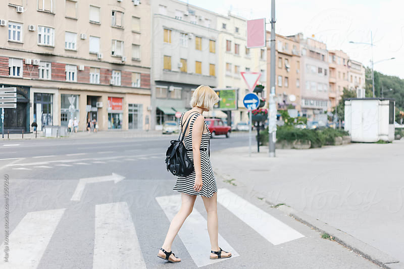 Young woman crossing the street by Marija Kovac for Stocksy United