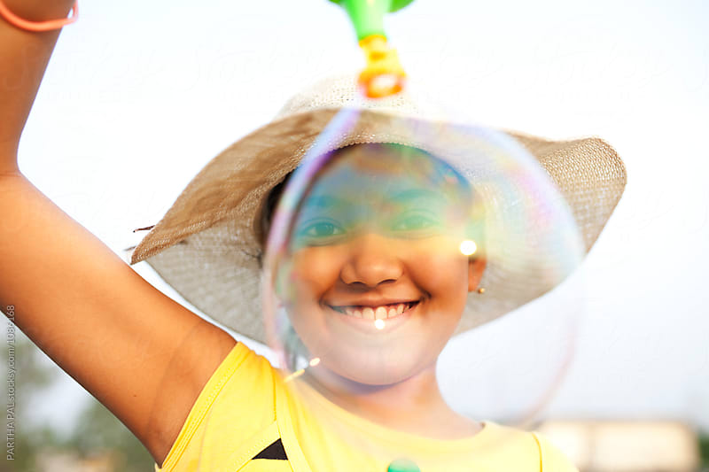 Teenage girl making fun with bubble by PARTHA PAL for Stocksy United