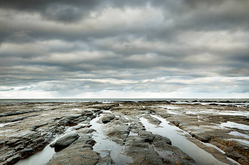 A rocky coastline at low tide by James Ross for Stocksy United