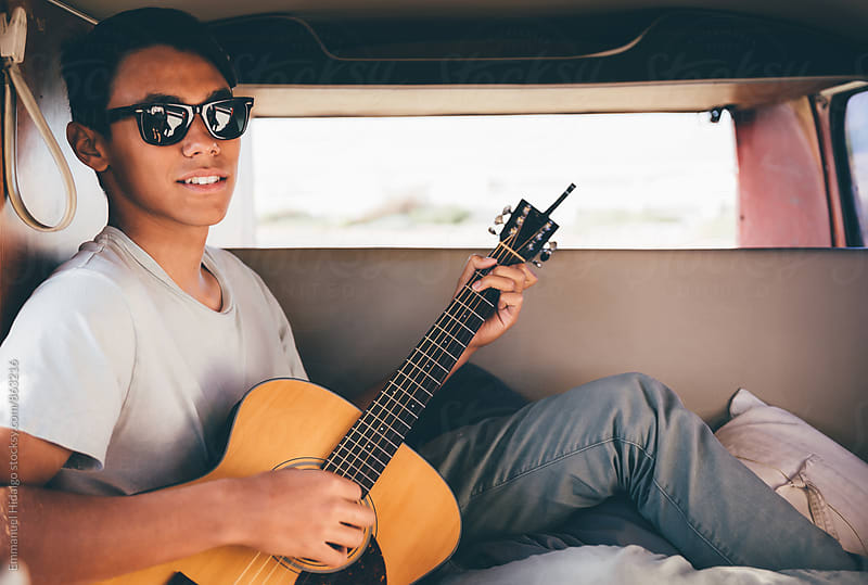 Young musician playing his guitar inside his vintage van by Emmanuel Hidalgo for Stocksy United