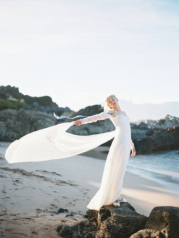 bride on beach with sweeping tulle standing on rocks by wendy laurel for Stocksy United
