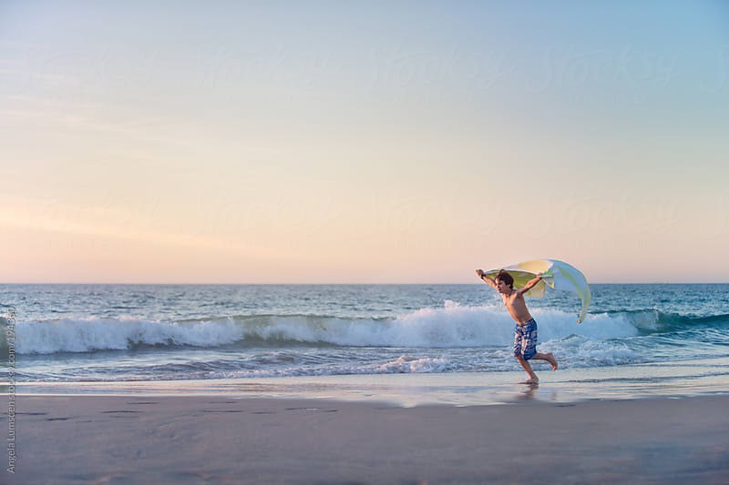 Boy running with a towel  at the beach at sunset by Angela Lumsden for Stocksy United