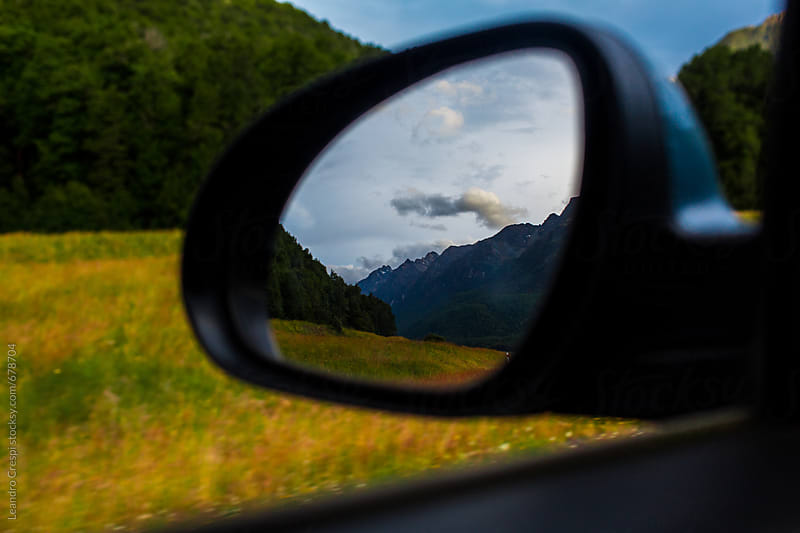 Mountains reflected in the left mirror of a moving car by Leandro Crespi for Stocksy United