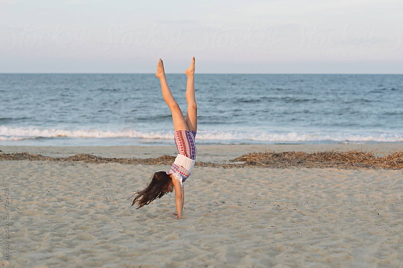 Young girl doing handstand on the beach by Preappy for Stocksy United