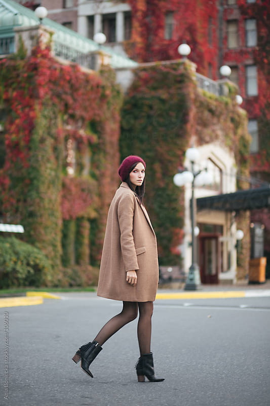 A  well dressed woman walking across the street in a camel color coat and a red beanie by Ania Boniecka for Stocksy United