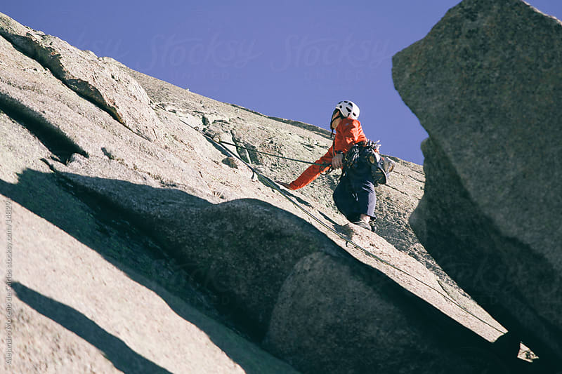 Man climbing on rock with harness and ropes by Alejandro Moreno de Carlos for Stocksy United