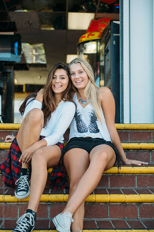 Two friends sitting on the steps and enjoying the day by Emmanuel Hidalgo for Stocksy United