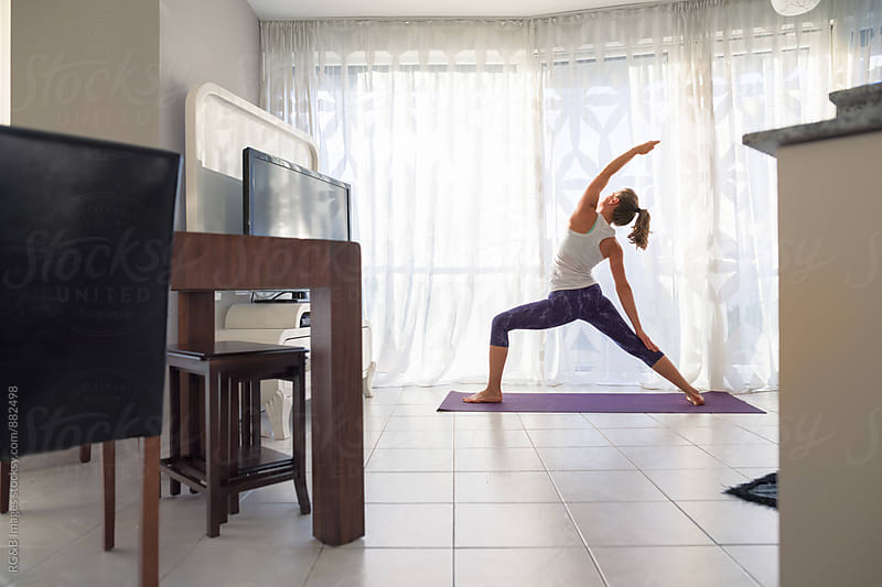 Woman doing yoga in the living room by RG&B Images for Stocksy United