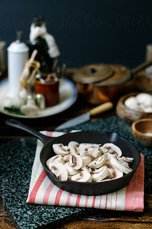 Sliced mushrooms in a cast iron frying pan, ready to be cooked. by Darren Muir for Stocksy United