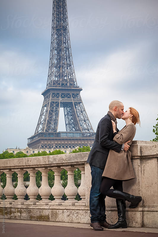Romantic couple in Paris kissing, Eiffel Tower in the background by Shelly Perry for Stocksy United