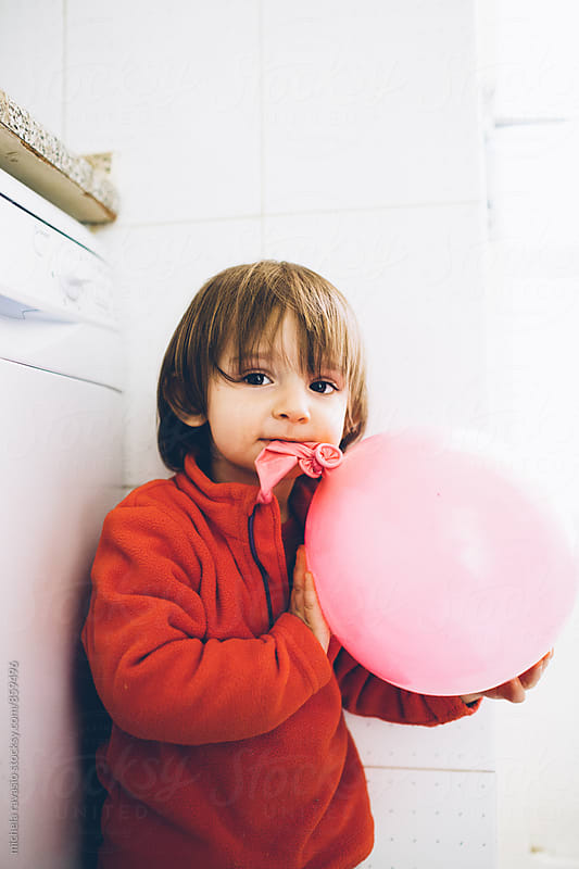 Little girl bites a pink balloon by michela ravasio for Stocksy United
