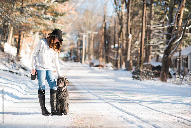 young woman standing with her dog on a snowy road by Léa Jones for Stocksy United