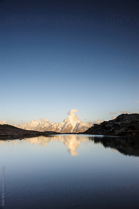 Mountain lake sunset: Bietschorn with mountain lake by Peter Wey for Stocksy United