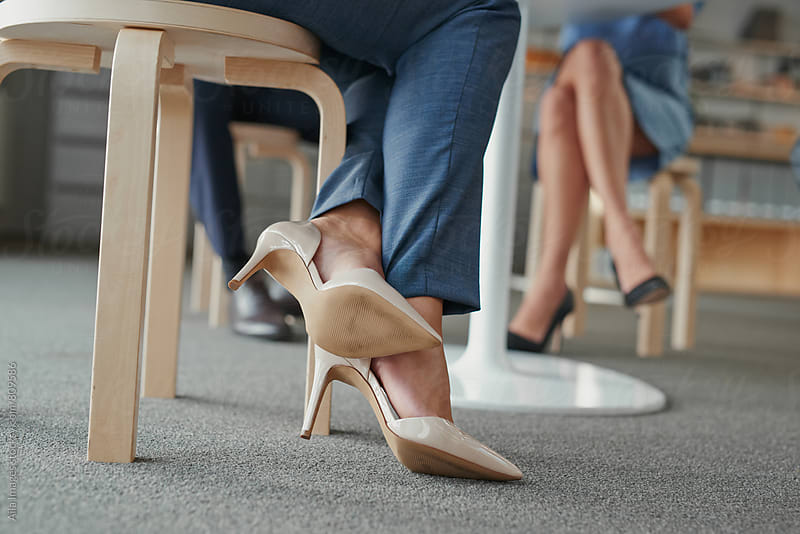 Close crop of womans feet wearing high heel shoes in corperate trendy office by Aila Images for Stocksy United