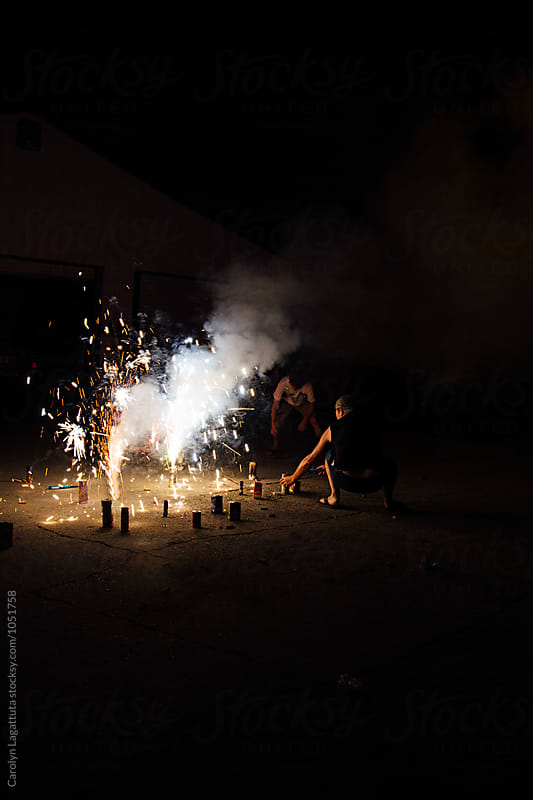 Two men lighting fireworks on the driveway by Carolyn Lagattuta for Stocksy United