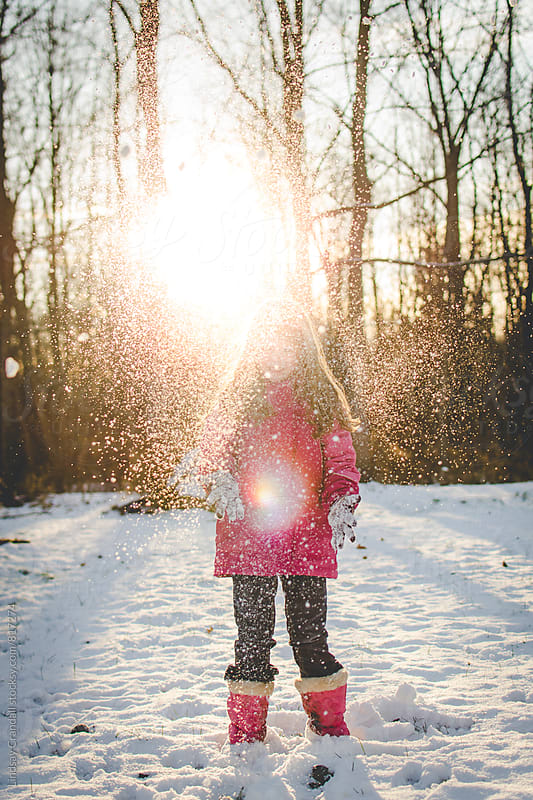 Snow falling on girl in the sun by Lindsay Crandall for Stocksy United