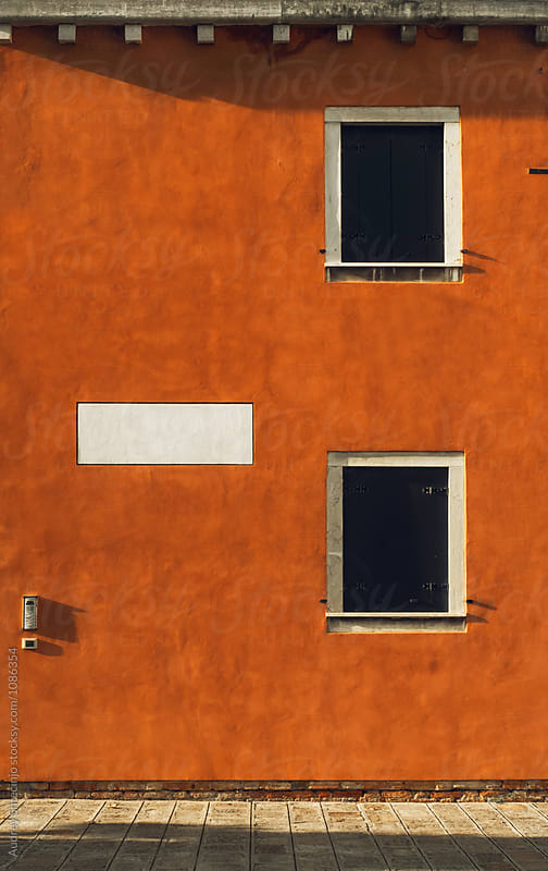 Old rustic orange facade with windows on sunny day.Venice/Italy by Marko Milanovic for Stocksy United