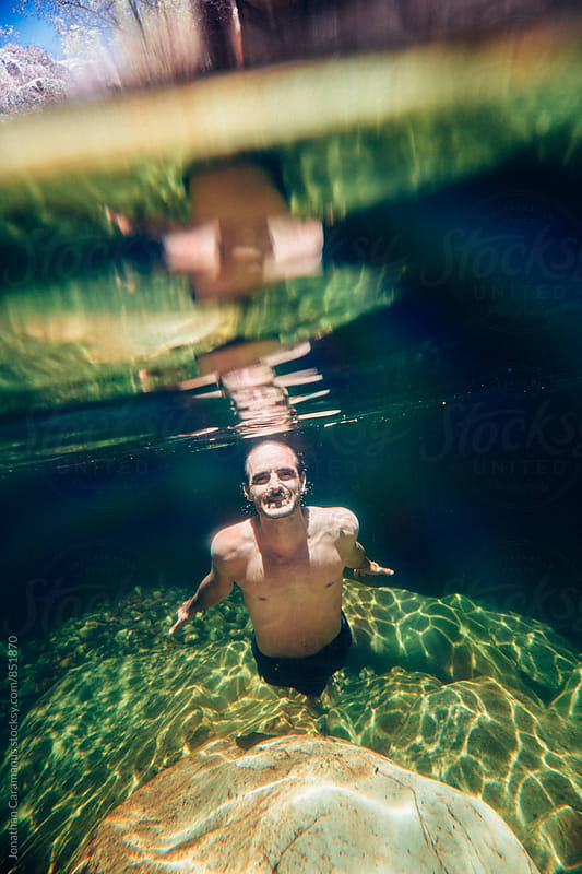Man swims underwater in crystal clear fresh river water rockpool by Jonathan Caramanus for Stocksy United