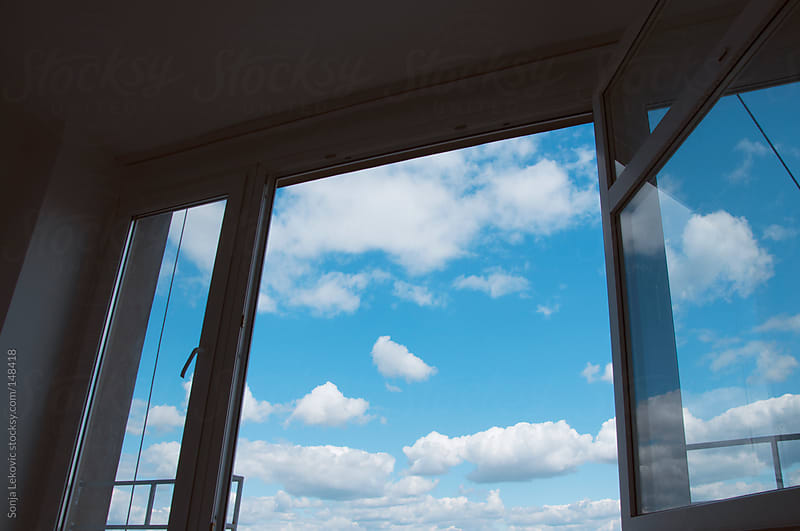 window and blue sky with clouds by Sonja Lekovic for Stocksy United