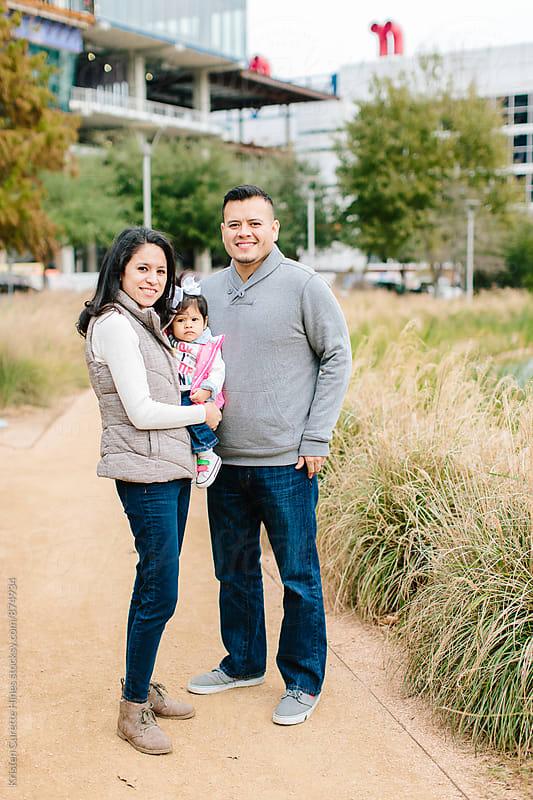 An adorable hispanic family posed outdoors at a park  by Kristen Curette Hines for Stocksy United