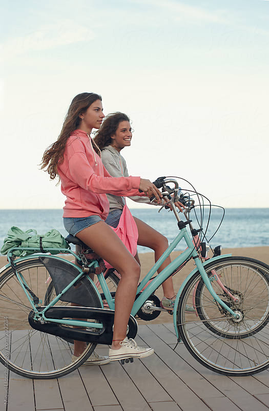 Two young girls  riding a bike by the beach after sunset by Miquel Llonch for Stocksy United