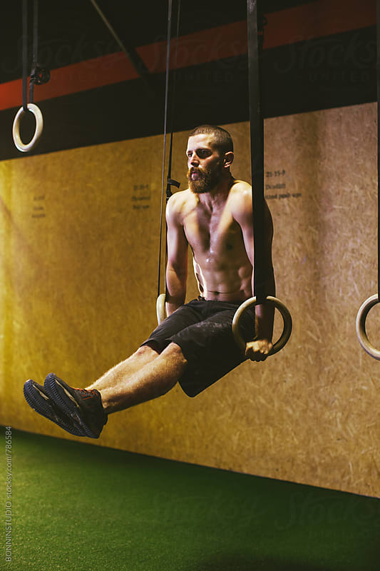 Bearded man training with rings in a gym box. by BONNINSTUDIO for Stocksy United