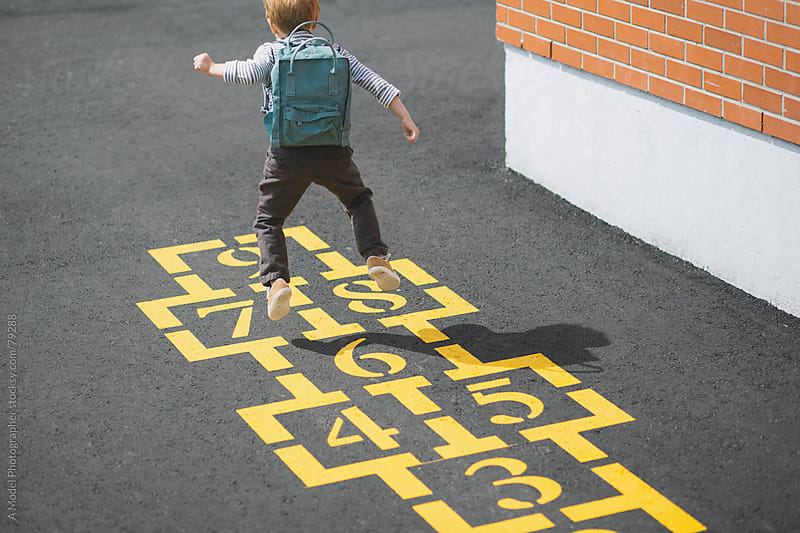 A boy skipping on the hopscotch at a school playground by Ania Boniecka for Stocksy United