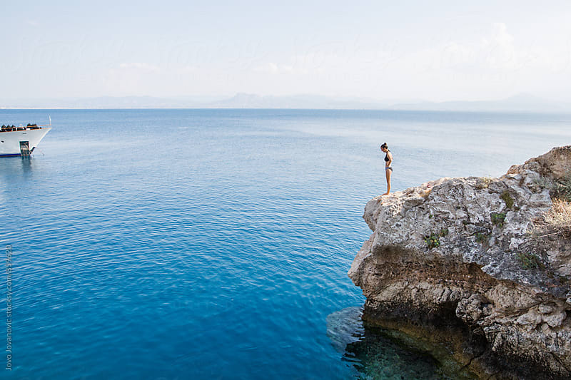 Woman in a bikini standing on a cliff overlooking the sea  by Jovo Jovanovic for Stocksy United