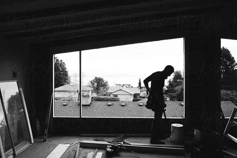 Carpenter contractor near window at home renovation by Rob and Julia Campbell for Stocksy United