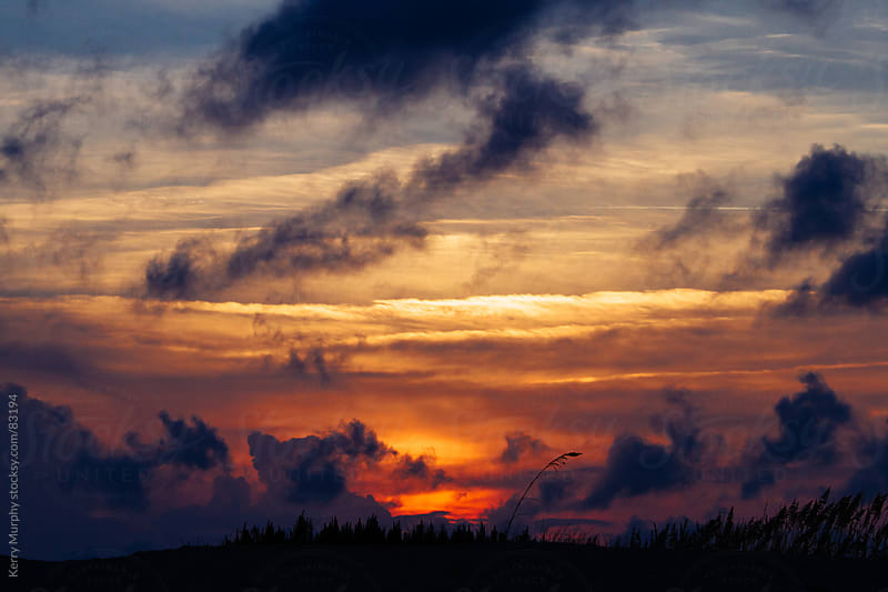 Colorful sunset and clouds over grassy dune by Kerry Murphy for Stocksy United