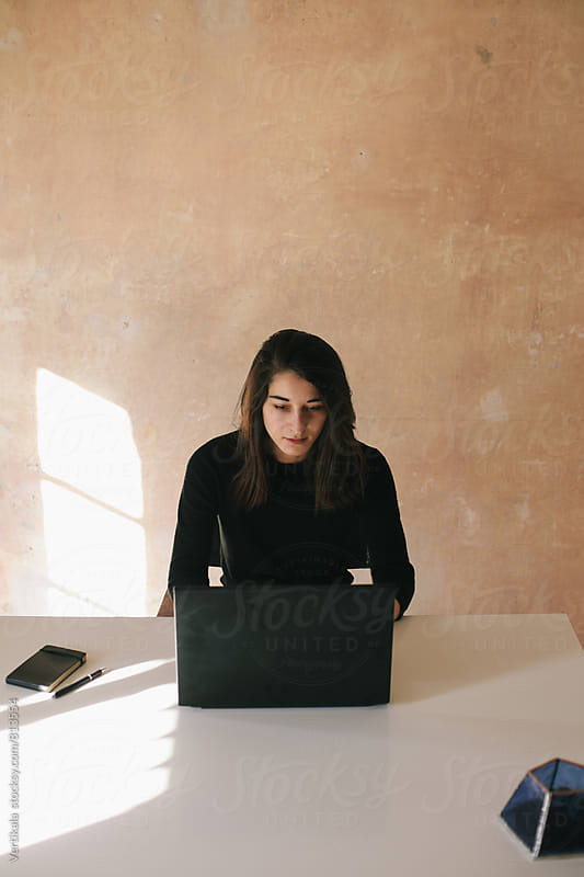 Beautiful brunette woman working on her laptop by VeaVea for Stocksy United