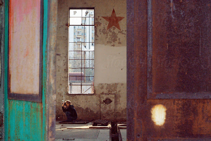 photographer smoking and taking pictures ,view trough the slightly open old,rusty,colorful door by Marija Anicic for Stocksy United
