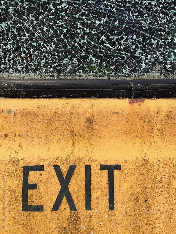 EXIT on car door, shattered window above by Paul Edmondson for Stocksy United