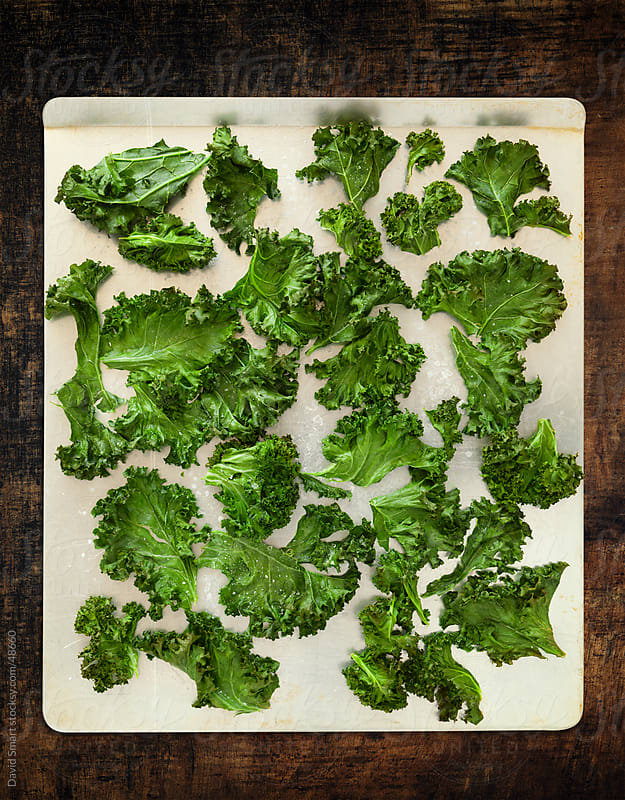 Kale chips on baking sheet cooling on dark wood table by David Smart for Stocksy United