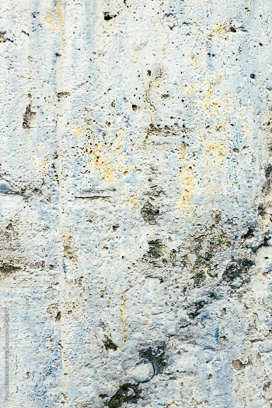 Close up peeling paint on worn, concrete wall by Paul Edmondson for Stocksy United