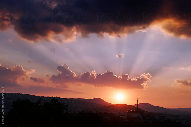 Setting sun with twighlight rays above hills by Ferenc Boros for Stocksy United
