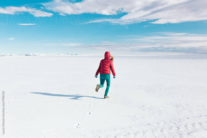 Person running through snow by Lucas Ottone for Stocksy United
