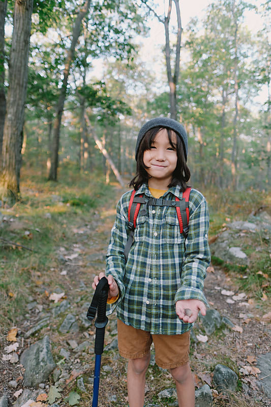 Cute young multiracial boy shows acorn he found by Kelli Seeger Kim for Stocksy United