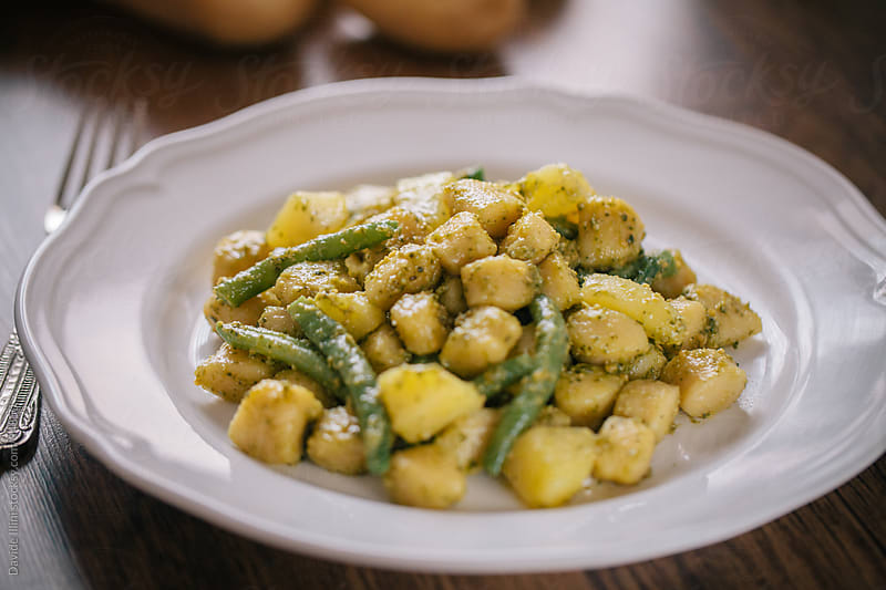 Gnocchi with pesto sauce potatoes and green beans. by Davide Illini for Stocksy United