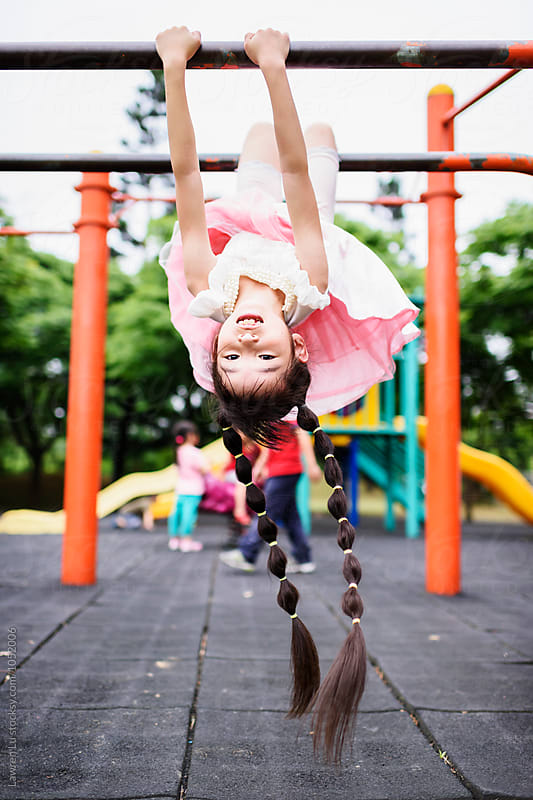 smiling girl hanging on bars at playground by Lawren Lu for Stocksy United