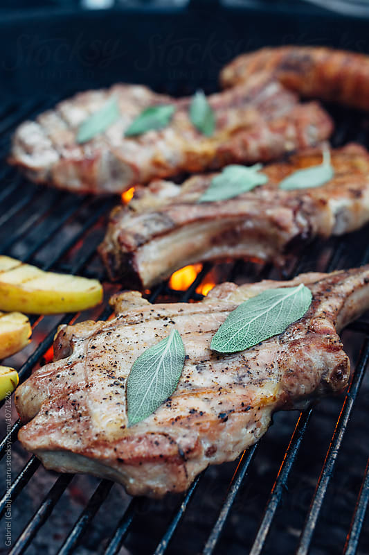 Pork chops on a charcoal grill by Gabriel (Gabi) Bucataru for Stocksy United