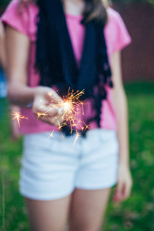 Young girl in white shorts holding a sparkler by Carolyn Lagattuta for Stocksy United