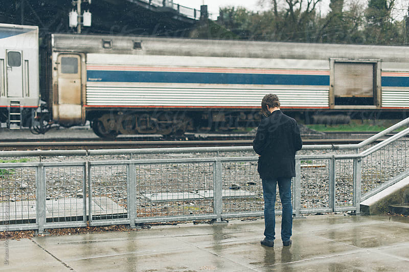 Man Waiting by Moving Train in Rain by Briana Morrison for Stocksy United
