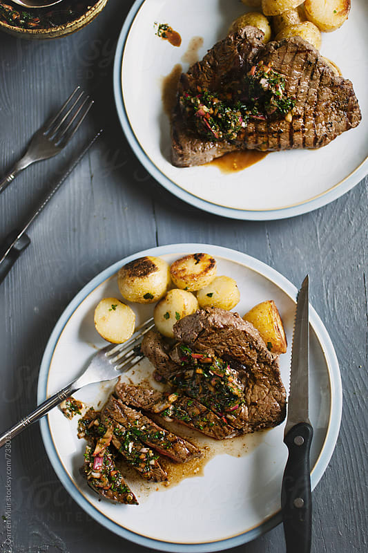 Rump steak with chimichurri sauce and roasted potato. by Darren Muir for Stocksy United