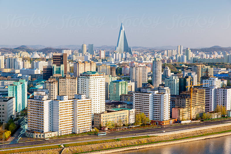 Democratic Peoples's Republic of Korea (DPRK), North Korea, Pyongyang, elevated city skyline including the Ryugyong hotel and Taedong river by Gavin Hellier for Stocksy United