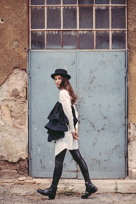 Woman wearing a hat in front of a blue vintage wall by Maja Topcagic for Stocksy United