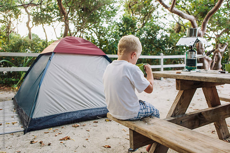 Boy Drinking Hot Chocolate At Campsite by Stephen Morris for Stocksy United