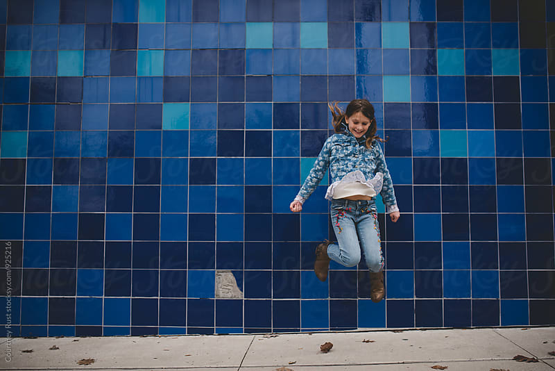 Jumping girl in front of blue wall by Courtney Rust for Stocksy United