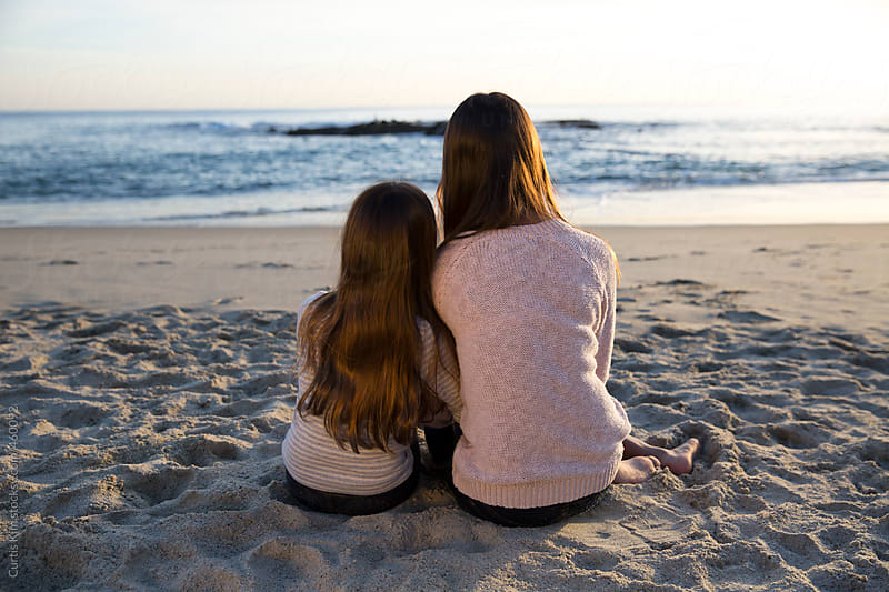 Two girls sitting on the beach during sunset by Curtis Kim for Stocksy United